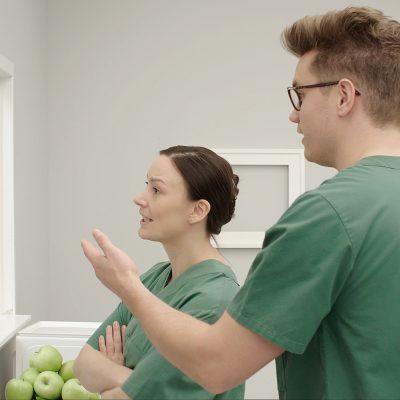 En man och en kvinna i sjukvårdskläder står och pratar schema.